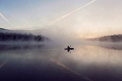 Young woman enjoys early morning paddle in kayak through mist on Daicey Pond in Maine's Baxter State Park, USA - p343m1569069 by Chris Bennett