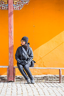 Tourist taking break on bench, Ulaanbaatar, Mongolia - p429m2069110 by Henn Photography