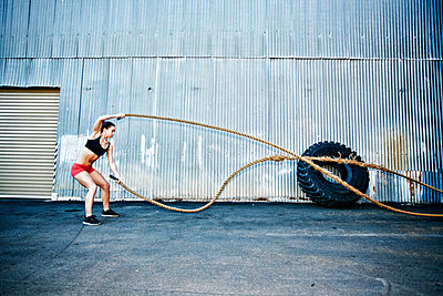 Mixed Race woman working out with heavy ropes outdoors - p555m1304128 by Peathegee Inc
