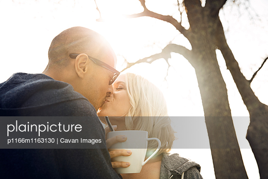 Low angle view of romantic couple kissing against clear sky on sunny day - p1166m1163130 by Cavan Images