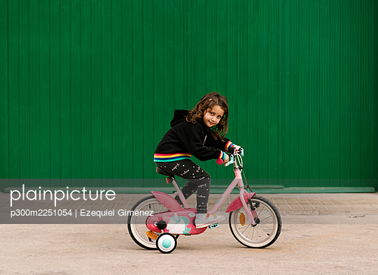 Girl riding bicycle on footpath against green wall - p300m2251054 by Ezequiel Giménez