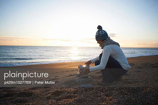Mature woman stacking stones on beach at dusk - p429m1027789f by Peter Muller