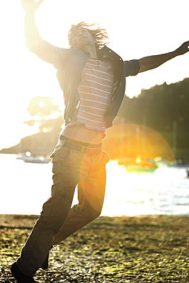 Young man jumping on a pebbly beach, arms raised, moored sailing boats in the background, sunlight. - p1100m2214263 by Mint Images
