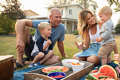 Young family enjoying picnic in yard - p1192m2047617 by Hero Images