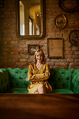 Portrait of smiling elegant woman sitting on a couch - p300m1549767 by Zeljko Dangubic