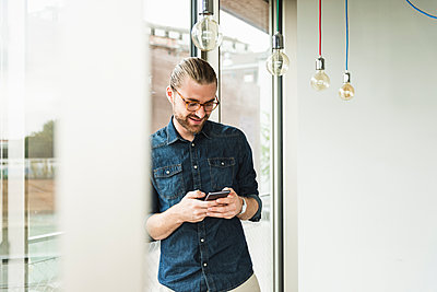 Smiling young businessman using cell phone at the window in office - p300m2043189 by Uwe Umstätter