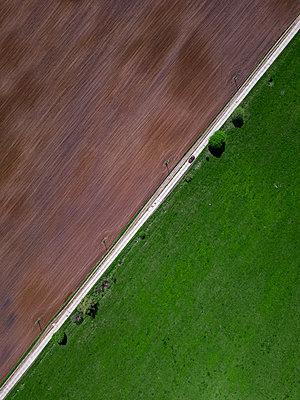 Aerial view of car driving along countryside road stretching between green and brown field - p300m2206829 by Konstantin Trubavin