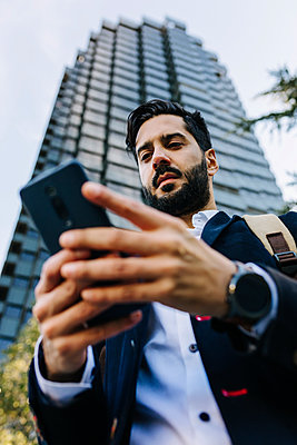 Businessman using mobile phone while standing in city - p300m2257510 by Xavier Lorenzo