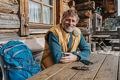 Smiling mature man with arms crossed sitting by backpack against cottage - p300m2266767 by Mareen Fischinger