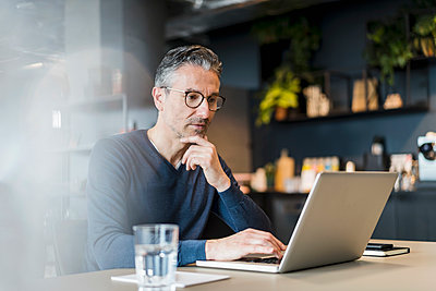 Male professional sitting with hand on chin using laptop at desk in office - p300m2287430 by Daniel Ingold