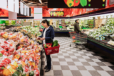 People buying groceries while standing in supermarket - p426m1148164 by Maskot