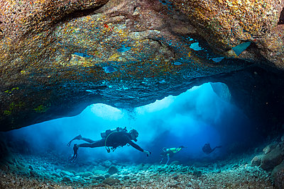 Divers inside a shallow tide pool canyon  area off the backside of Lanai near Kaumalapau Harbor, Hawaii. Aerated surf materializes as clouds when waves pour into the area and pockets of exhaled air appear as reflective mercury on the ceiling; Lanai, Hawai - p442m2074275 by Dave Fleetham