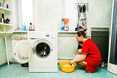 Caucasian woman hand-washing laundry - p555m1306361 by Aleksander Rubtsov