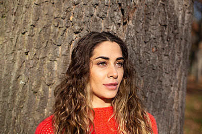 Young woman leaning against tree trunk - p975m2222114 by Hayden Verry