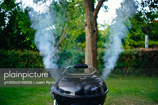 Smoking grill in the garden - p1053m2168306 by Joern Rynio