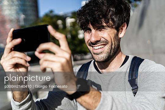 Happy man taking a selfie in the city - p300m2140410 von Giorgio Fochesato