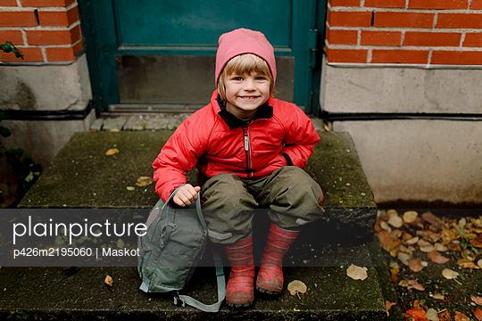 Portrait of smiling boy in warm clothing sitting on steps - p426m2195060 by Maskot