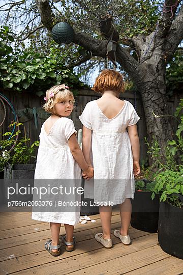 Zwei Schwestern Hand in Hand auf der Terrasse - p756m2053376 von Bénédicte Lassalle