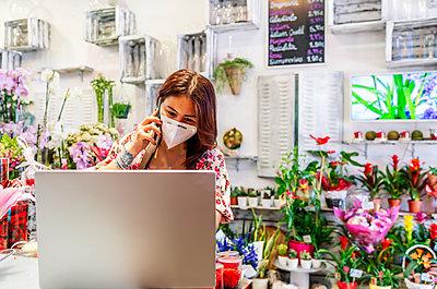 enterprising woman receiving an order by phone - p1166m2279529 by Cavan Images