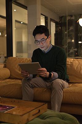Businessman sitting on sofa and using digital tablet - p1315m2041147 by Wavebreak