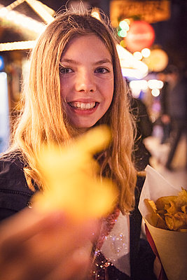 Portrait of smiling blond girl eating potato chip at carnival in city during night. Munich, Germany - p300m2197470 by Studio 27