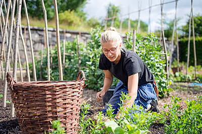 Young woman working in garden - p312m1103593f by Karl Forsberg