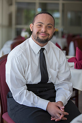 Mixed race server with down syndrome smiling in restaurant - p555m1311481 by Disability Images