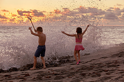 Rear view of boy and sister playing in splashing waves at sunrise, Blowing Rocks Preserve, Jupiter Island, Florida, USA - p924m1157823 by Kinzie Riehm