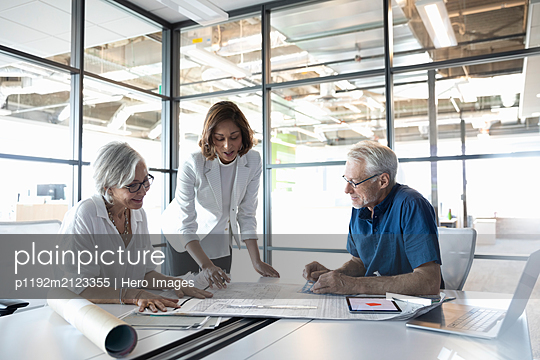 Clients discussing plans with design professional in studio - p1192m2123355 by Hero Images