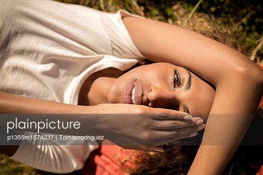 Junge Frau macht eine Pause beim Wandern - p1355m1574237 von Tomasrodriguez