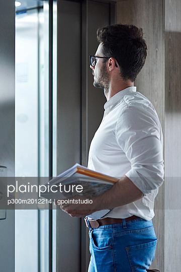 Businessman with magazines entering the elevator - p300m2012214 von gpointstudio