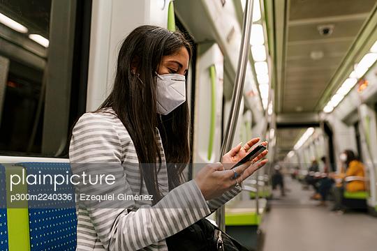 Female passenger text messaging through smart phone in metro train - p300m2240336 by Ezequiel Giménez
