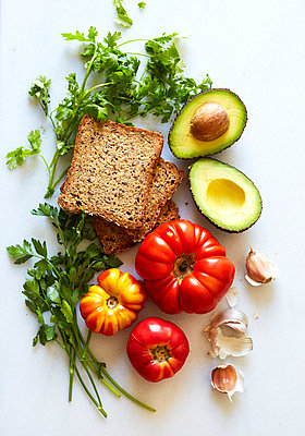 Overhead view of bread, avocado and vegetables over white background - p1166m1489964 by Cavan Images
