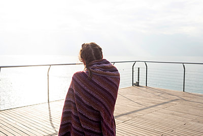 Rear view of young woman wrapped in blanket looking out to sea - p1166m2096209 by Cavan Images