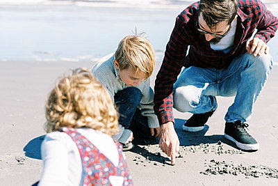 Father and son drawing in the sand on a beach in Massachusetts - p1166m2212919 by Cavan Images