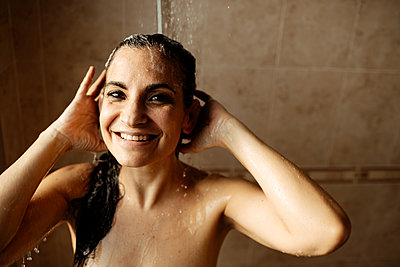 Portrait of adult woman smiling while taking shower - p300m2266253 by Gala Martínez López