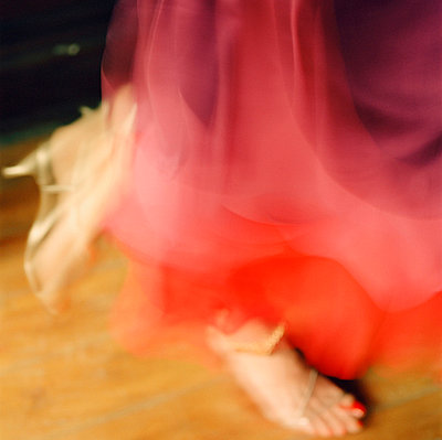 Atmospheric detail of a woman's feet in a red dress dancing  - p349m695150 by Emma Lee