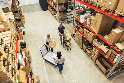 High angle view of coworkers working together in distribution warehouse - p426m1580295 by Kentaroo Tryman