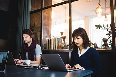 Confident female and male entrepreneurs using laptops at desk in office - p426m2088973 by Maskot