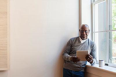 Man using digital tablet near window - p555m1303737 by Strauss/Curtis