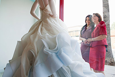 Mother and daughter looking at wedding dress in shop window - p9242304f by Image Source
