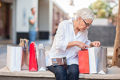 Mature woman peering into shopping bags at shopping mall - p924m1139380 by Zero Creatives