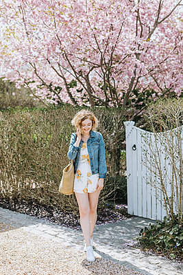 Young woman with straw bag in front of pink tree blossom, Menemsha, Martha's Vineyard, Massachusetts, USA - p924m2058141 by Lena Mirisola