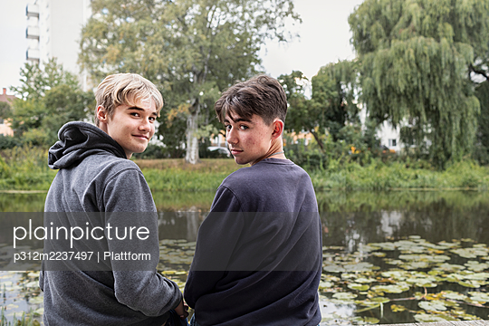 Two teenage boys sitting together - p312m2237497 by Plattform