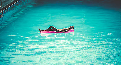 High angle view of a young woman lying on a pool raft in a swimming pool. - p1100m1482302 by Mint Images