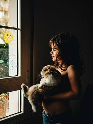Little girl carries rabbit in her arms at the window  - p1522m2176540 by Almag