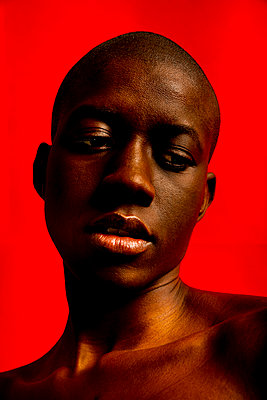 Portrait of a young black bald woman with a red background - p1619m2192692 by Laurent MOULAGER