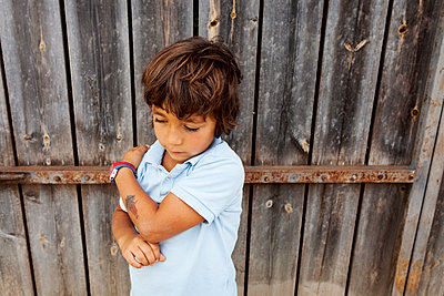 Serious little boy leaning against old wooden door - p300m1189168 by Valentina Barreto