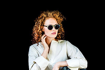 Portrait of stylish young woman with curly red hair wearing sunglasses in front of black background - p300m2029048 by Jo Kirchherr