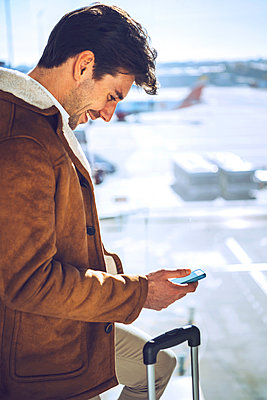 Happy businessman using smart phone by window at airport departure area - p300m2202600 by klublu
